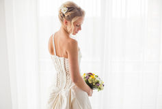 Bride standing by the window with flowers in her hand Royalty Free Stock Images
