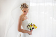 Bride standing by the window with flowers in her hand Royalty Free Stock Photo
