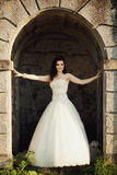 Bride stands in the arch of the ancient castle.  Royalty Free Stock Photo