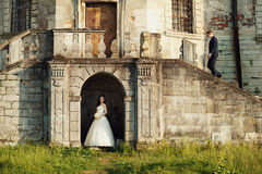 Bride stands in the arch of the castle while groom walking up by stairs Stock Photos