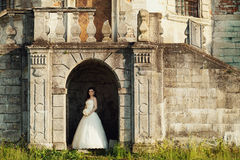 Bride stands in the arch of the castle shined by sunny rays.  Royalty Free Stock Photography