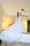 Bride stands on bed lifting her bouquet Royalty Free Stock Images