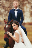 Bride stands behind a horse while groom sits on its back Stock Images