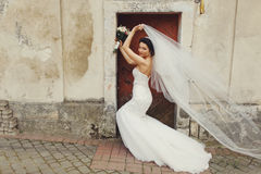 Bride stands behind an old door while wind blows away her veil. A Royalty Free Stock Images