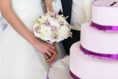 Bride stands behind a wedding cake holding a bouquet in her hand. S Stock Images
