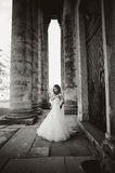 Bride stands between the columnes Royalty Free Stock Photo