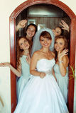 Bride stands in doors surrounded by bridesmaids.  stock image