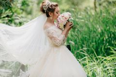 The bride stands in a field with high green grass and enjoys the aroma of her wedding bouquet of flowers. The girl`s fad. Develops in the gusts of a summer wind royalty free stock photo