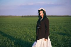 The bride is standing in a field at sunset, wearing a knitted sweater, a cold evening royalty free stock photography