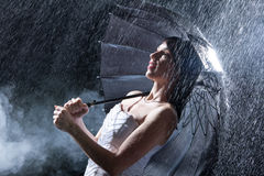 Bride stands on heavy rain late at night. Stock Photos