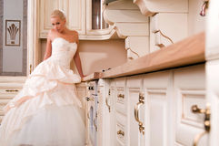 Bride stands in the kitchen and laughs Stock Image