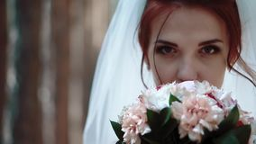 Bride stands near trees in the forest, brings a bouquet of flowers to face and looks at the camera, portrait, close-up stock video footage
