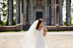 Bride stands next to the old church Stock Image