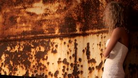 Bride Stands Next To A Rusty Wall. The bride in a wedding dress, stands and looks at old and rusty wall. Motion zoom stock video footage