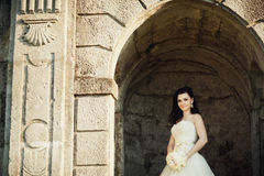 Bride stands in the stone arch of the castle.  Royalty Free Stock Photos
