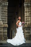 The bride stands at the stone wall royalty free stock photography