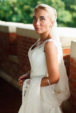 Bride stands straight holding veil in her hands Royalty Free Stock Photos