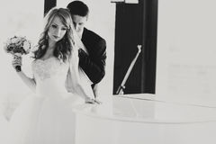 Bride stands thoughtful behind a piano while groom hugs her from Royalty Free Stock Images
