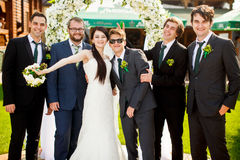 Bride stands together with funny groomsmen.  Stock Photo