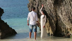 Bride stands in water against rock and groom comes and hugs. Brunette bride stands in transparent shallow water leans on cliff and groom comes to her and hugs stock video footage