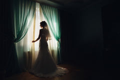 Bride stands before the window covered with green curtains.  Stock Photo