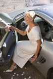 Bride stepping out of car, smiling, elevated view Stock Photos