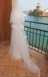 Bride stood on balcony in tropical coastal resort Stock Image