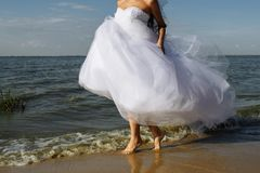 The bride runs on the surf line royalty free stock image