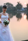 Bride on sunset. Bride holding her bouquet on a lake in sunset Royalty Free Stock Photography