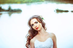 Bride at sunset on the river. Young beautiful woman in white wedding dress at blue river background closeup portrait Royalty Free Stock Photography