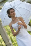 The bride Sveta. The bride with an umbrella at an ancient column in park Royalty Free Stock Photography