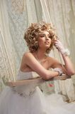 Bride on Swing. Blond bride holding on a swing and looking in the distance Royalty Free Stock Images