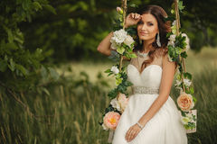 Bride swinging on a swing decorated with flowers. Royalty Free Stock Photo