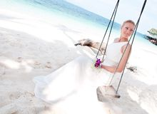 Bride swinging on tropical sea side background royalty free stock images