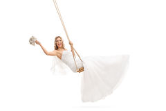 Bride swinging on a wooden swing. Carefree young bride swinging on a wooden swing and holding a wedding flower isolated on white background Stock Image