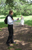 Bride takes off running from groom. A bride in a wedding gown runs down a path away from her groom, left holding the wedding ring Stock Photography