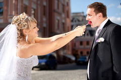 Bride taking lollipop from groom while he was eating it Stock Photo