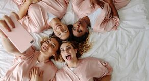 Bride taking selfie with bridesmaids making funny faces Stock Photo