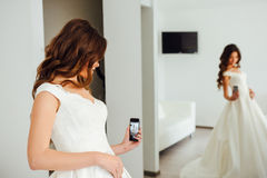 Bride are taking a selfie with mirror reflection. Bride are taking a selfie royalty free stock image