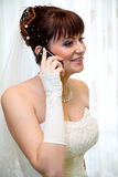 Bride talking on mobile phone. Young beautiful bride talking on mobile phone royalty free stock photo