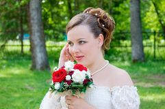 Bride talking on phone and beautiful bouquet. Bride talking by phone with beautiful bouquet of roses. Her wedding day Stock Images