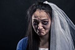 Bride with tear-stained face on black background. Disheveled bride with tear-stained face on black background. Studio photo shoot Stock Images