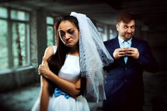Bride with tearful face and groom with sly smile Stock Image
