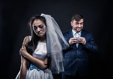 Bride with tearful face and groom with sly smile. Bride with tearful face, groom with sly smile on background. Unhappy marriage Royalty Free Stock Photos