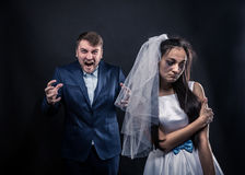 Bride with tearful face and terrible brutal groom. In suit, studio photo shoot, black background Royalty Free Stock Photography