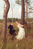 Bride threatens your wedded husband with a stick. Young bride threatens your wedded husband with a stick, standing on a meadow between two trees royalty free stock photo
