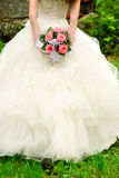 Bride throw bouquet. Bride from behind throw the bouquet from pink roses on old wall background stock photos