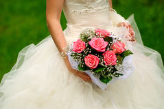 Bride throw bouquet. Bride from behind throw the bouquet from pink roses on old wall background royalty free stock images