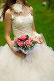 Bride throw bouquet. Bride from behind throw the bouquet from pink roses on old wall background royalty free stock photography