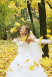 Bride throwing autumn leaves Royalty Free Stock Photos